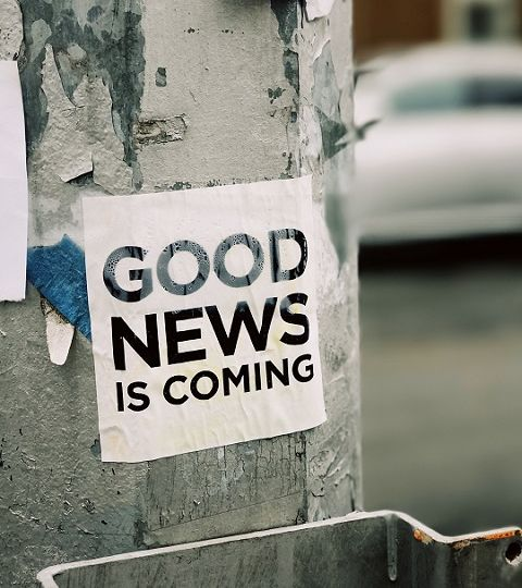 """A lamppost with peeling paint and a black and white notice pasted to it reading """"Good news is coming""""."""