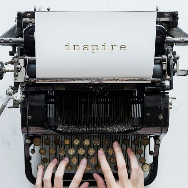 Black typewriter with person's fingers on the keys and the word 'Inspire' showing on the paper in the roller. Photo by rawpixel.com from Pexels
