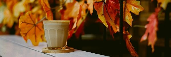 Brown ceramic mug on a coaster placed on wooden table with colourful autumn leaves trailing behind.