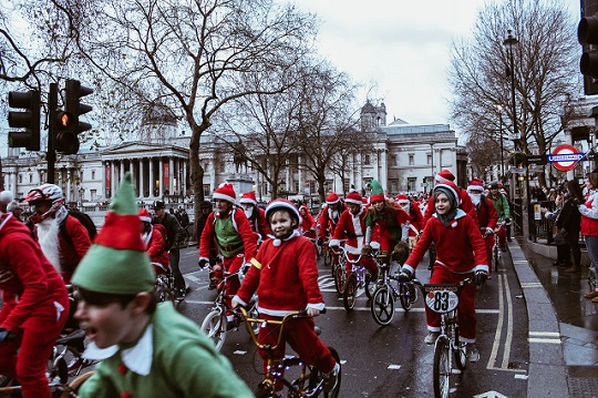 Lots of children and adults on bikes, in Santa and Elf outfits in Trafalgar Square, London.