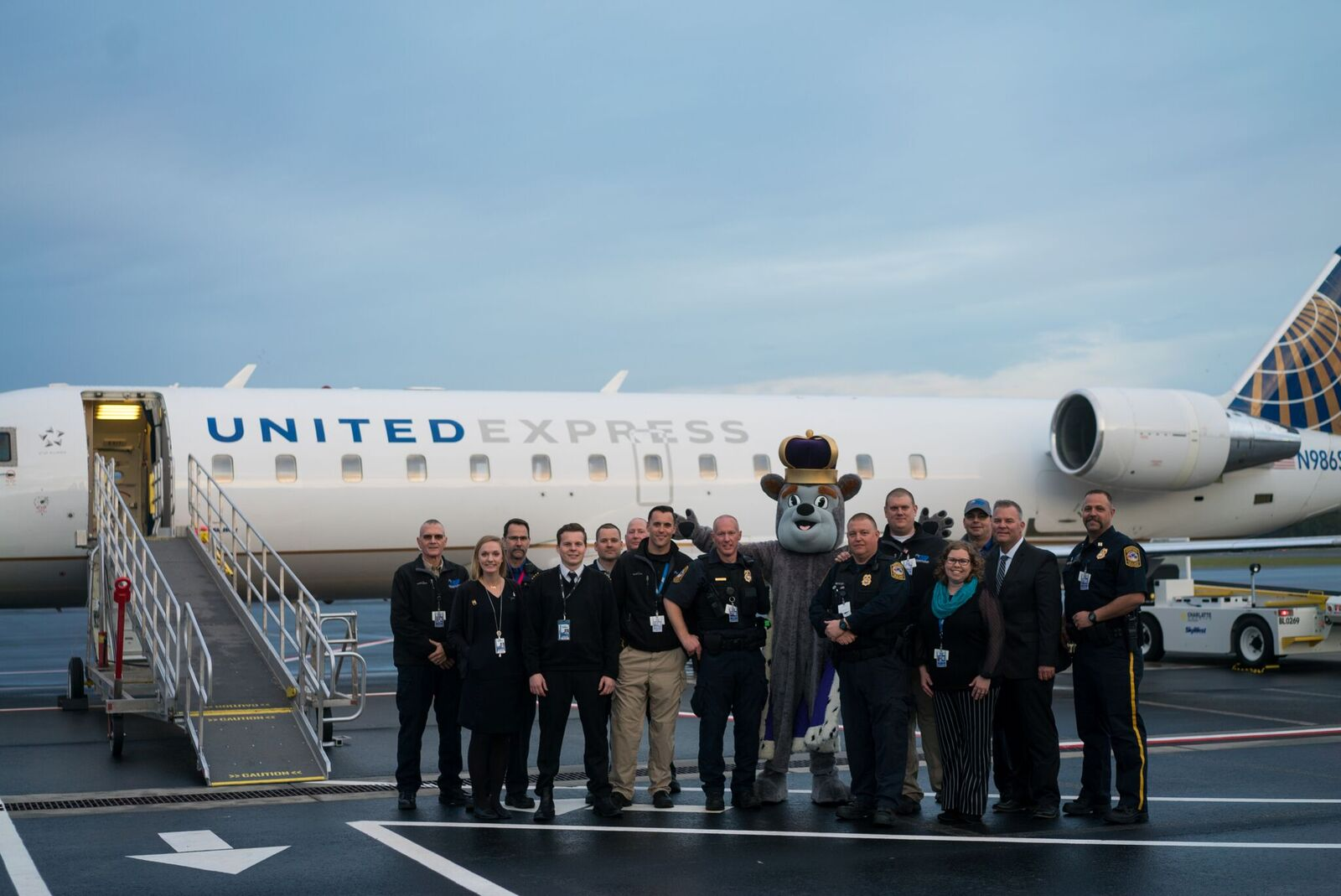 JMU Duke Dog and SHD staff standing in front of a United jet.