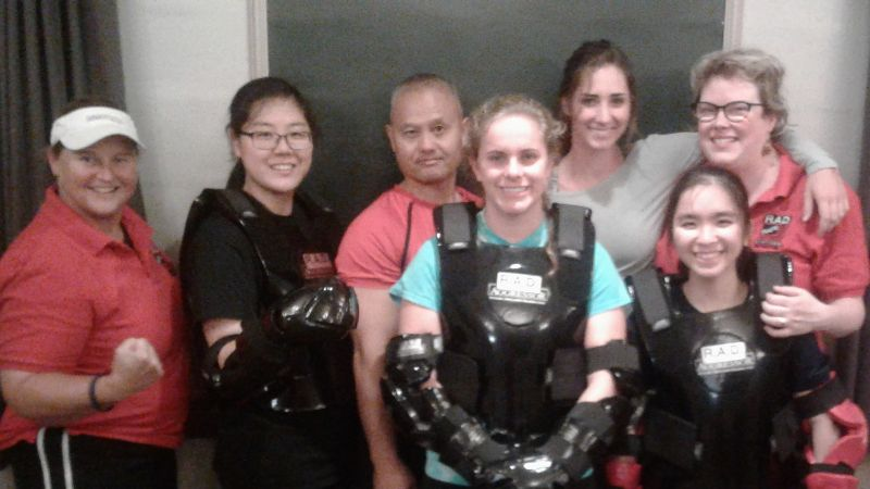 Women in padded gear at defense training class, smiling
