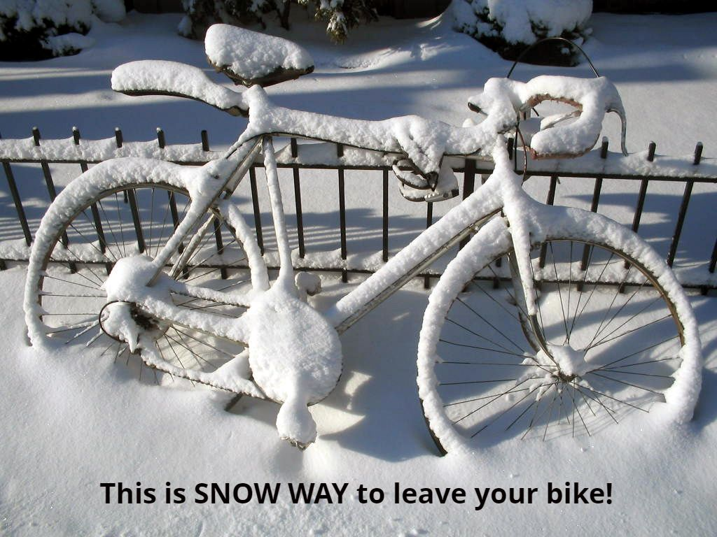 Bicycle covered in snow locked to fence