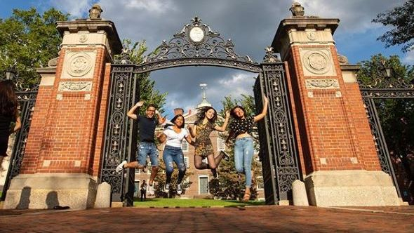 Four smiling students jumping under the Van Winkle Gates