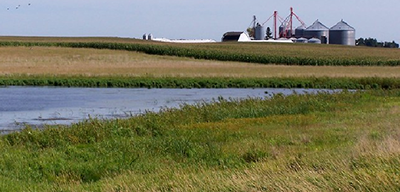 Photo showing farm building in background with pond and farm fields in foreground.