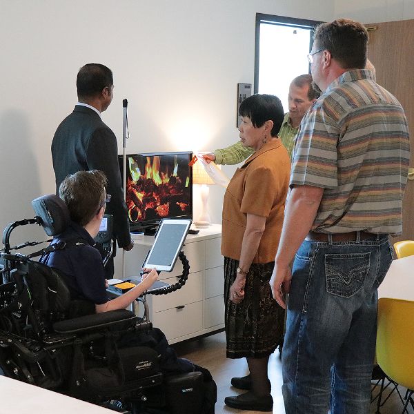 A group of people gathers around the TV as smart home technology is demonstrated.