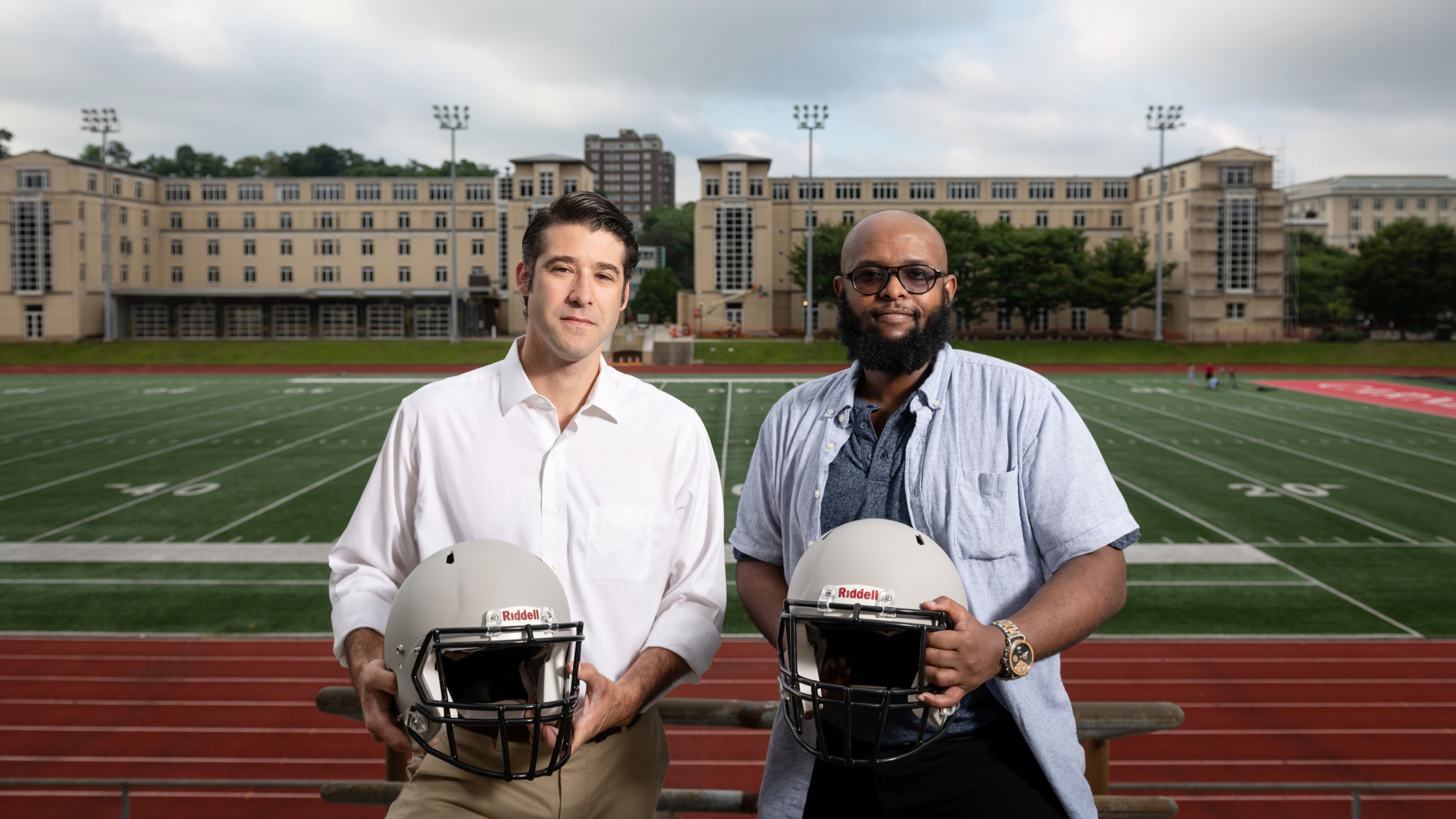 Brad Mahon and Adnan Hirad pose with football helmets in front of a football field.