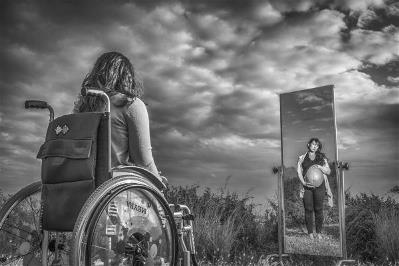 Woman in wheelchair looking through a mirror at a pregnant woman without disability