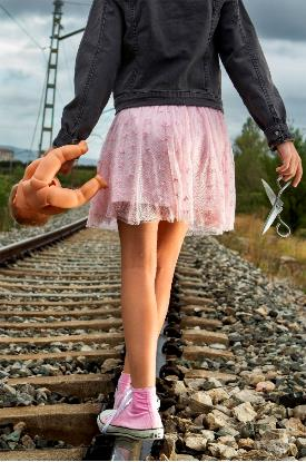 Young girl walking on train lines holding a plastic doll on her left hand and a pair of scissors on the right hand
