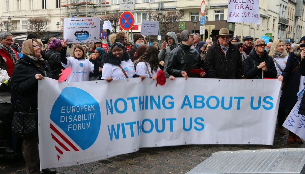 """Activists during the demonstration holding a banner that says """"Nothing About Us WIthout Us"""""""