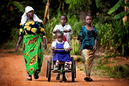 Woman and three children walking. One of the children is in a wheelchair. (Copyrights: CBM UK)