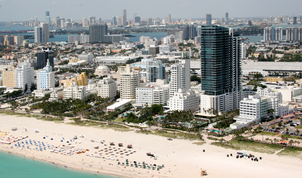 An aerial view of Miami Beach: several high-rise buildings with a city in the background