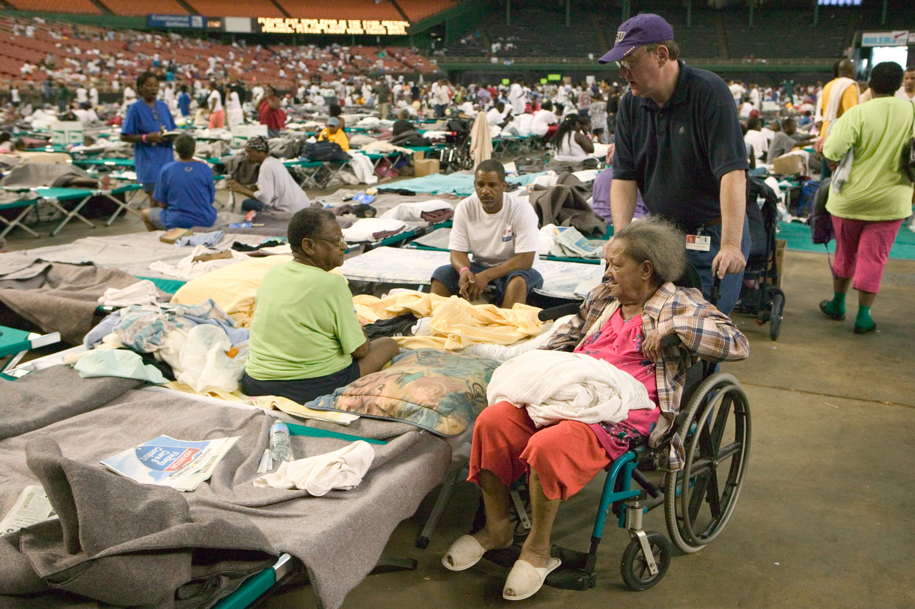 An African-American elderly woman in a wheelchair being pushed around speaks to 2 other individuals. The others are sitting cots on the floor of a large stadium. There are dozens of cots laid out in rows in the background, with scattered blankets and many people sitting down and walking around.