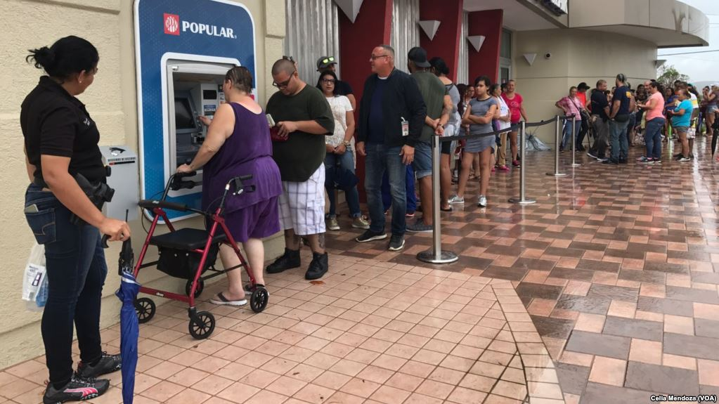 Residents of Ponce, Puerto Rico, line up at an ATM in hopes of getting some cash. A woman with a walker is at the front of the line