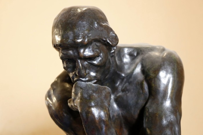 A statue of a man thinking, with his chin resting on his hand