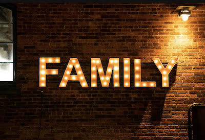 The word Family in lights on a brick wall