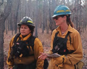 Two women in hardhats and nomex firefighting clothes working on a fire