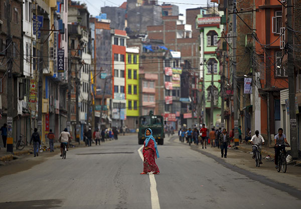 A woman cross the deserted road during the general strike called by the hardliner faction from the former Maoist rebels to protest against the first draft of the new constitution that has been published in Kathmandu, 24 July 2015. REUTERS/Navesh Chitrakar