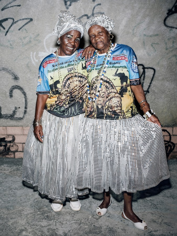 Two smiling women in matching outfits. Photo by Wayne Lawrence.