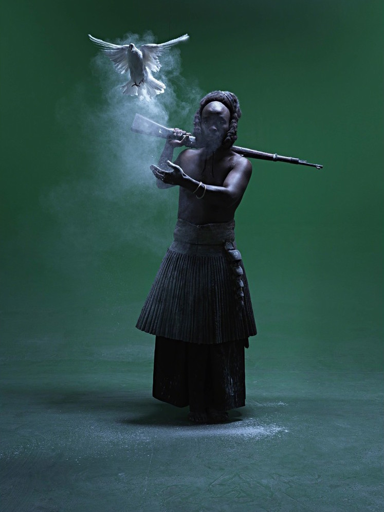 A green background. The dark-skinned subject holds a rifle and releases a dove.