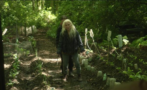 two women approach the survivalist's cabin, through his garden
