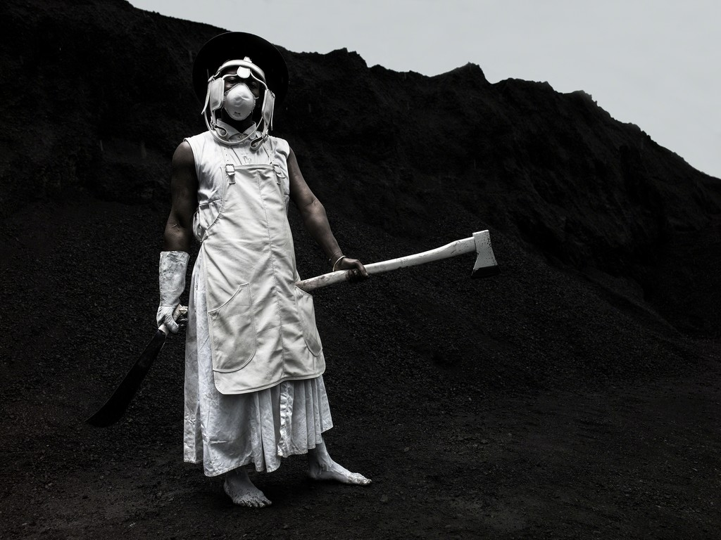 A person dressed in white, wearing makeshift safety equipment, and holding a white axe.