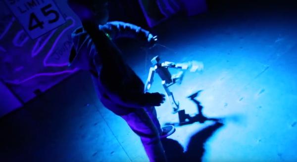 a young man making a robot puppet breakdance
