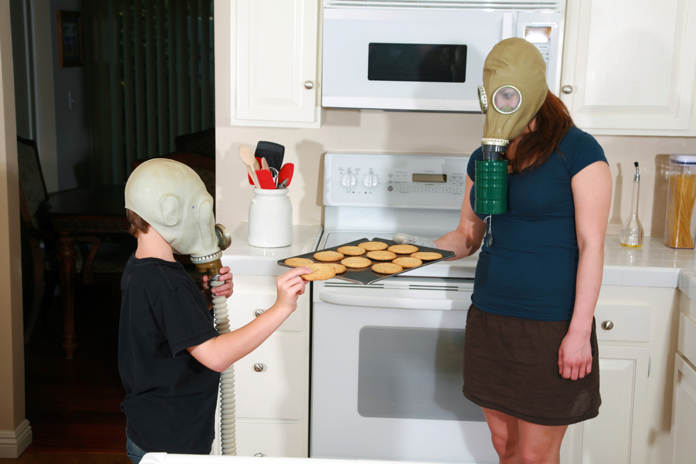 Mother and son wearing gas masks.