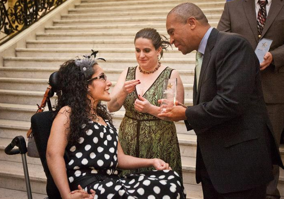 Caroline Horvitz receiving the 29 Who Shine Award from Massachusetts Governor Deval Patrick with her sign language interpreter standing by