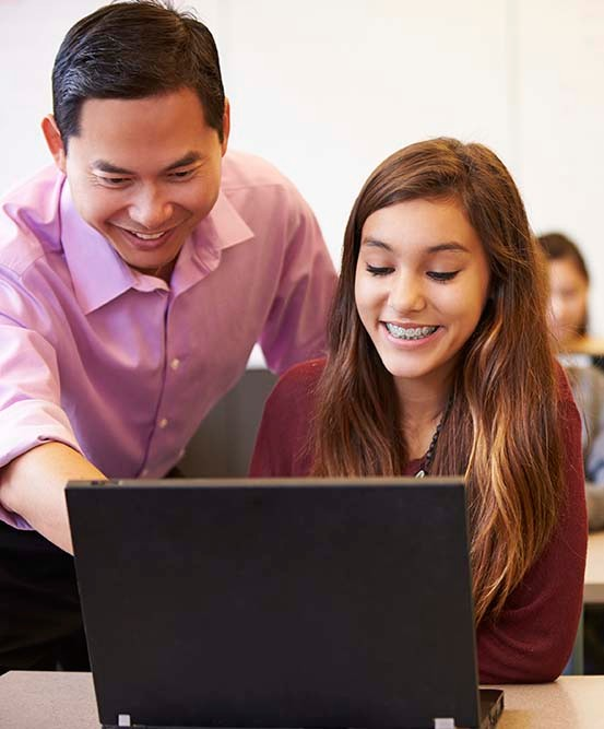 teacher working with student on laptop