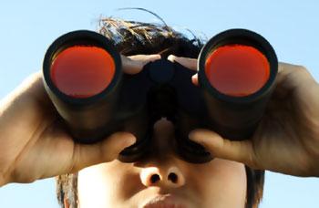 Person looking thru binoculars