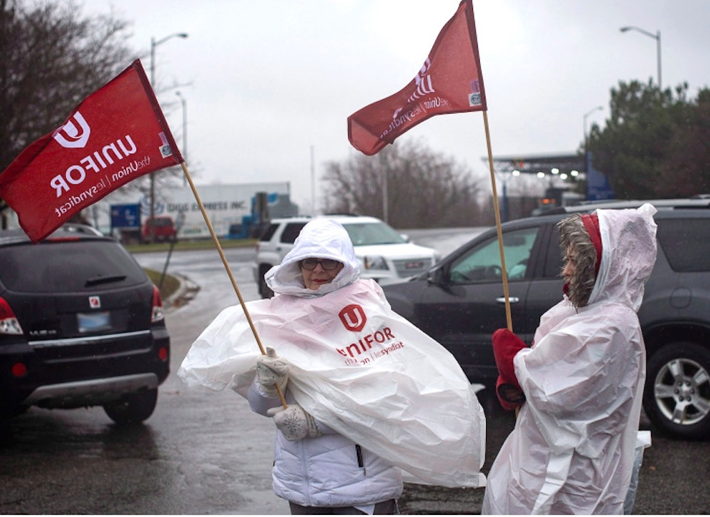 Canadian GM workers protesting plant closure on a windy day.