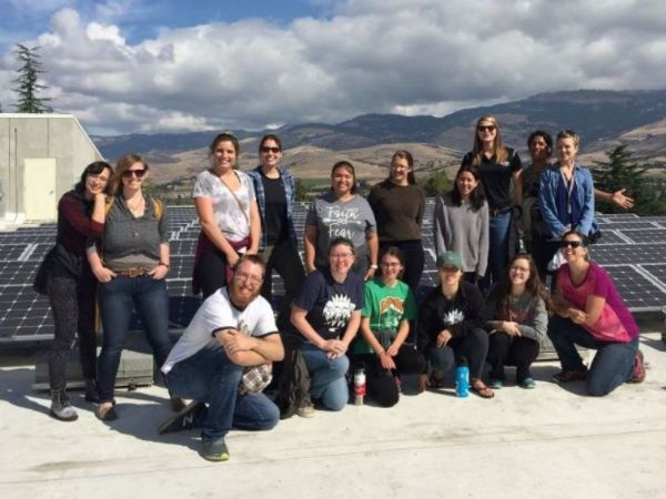 Group of students and staff on top of building with solar panels at SOU
