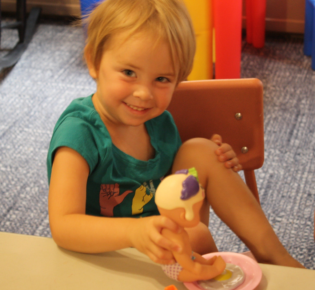 Three-year-old smiles while sitting doll on a plate with a rubber egg on it.