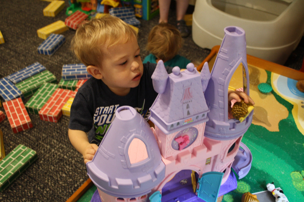 LIttle boy pushes plastic animal out of Fisher Price castle window.
