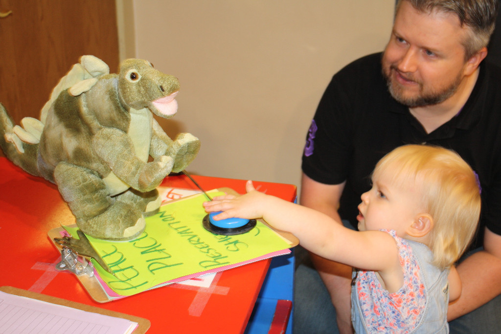 Little blond toddler presses a switch to activate a stuffed dinosaur.