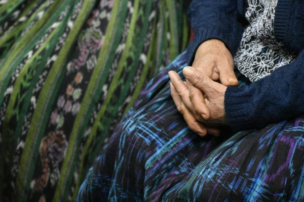 Her hands folded over her skirt, a survivor of sexual violence waits outside of the courtroom for the Military Zone 21 case.