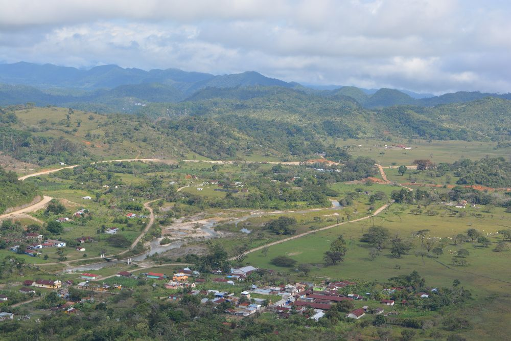 Ixquisis, Huehuetenango, Guatemala. A village in rolling green hills that lead to mountains in the background.