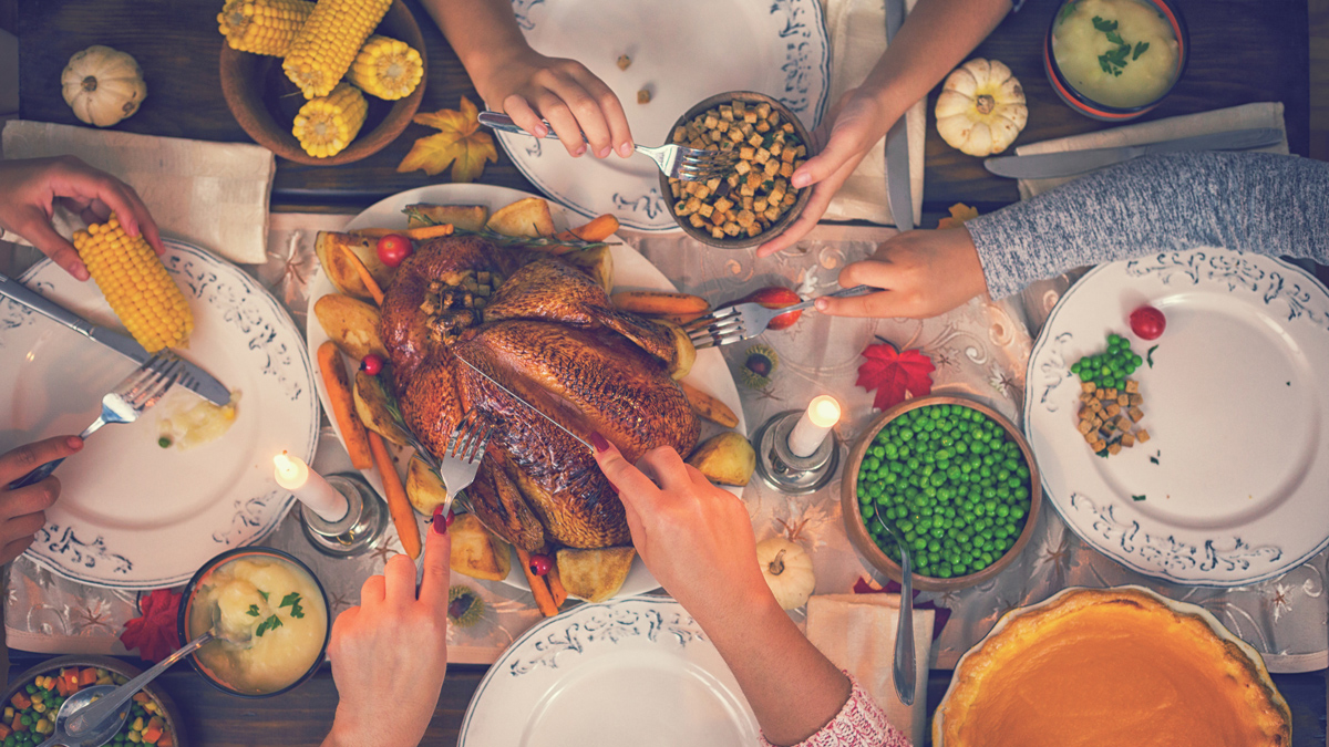 Hands are reaching over a dinner table filled with plates and foods like turkey, corn on the cob and peas for Thanksgiving.