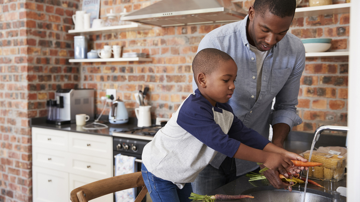 A father is showing his son how to properly wash a carrot at the kitchen sink