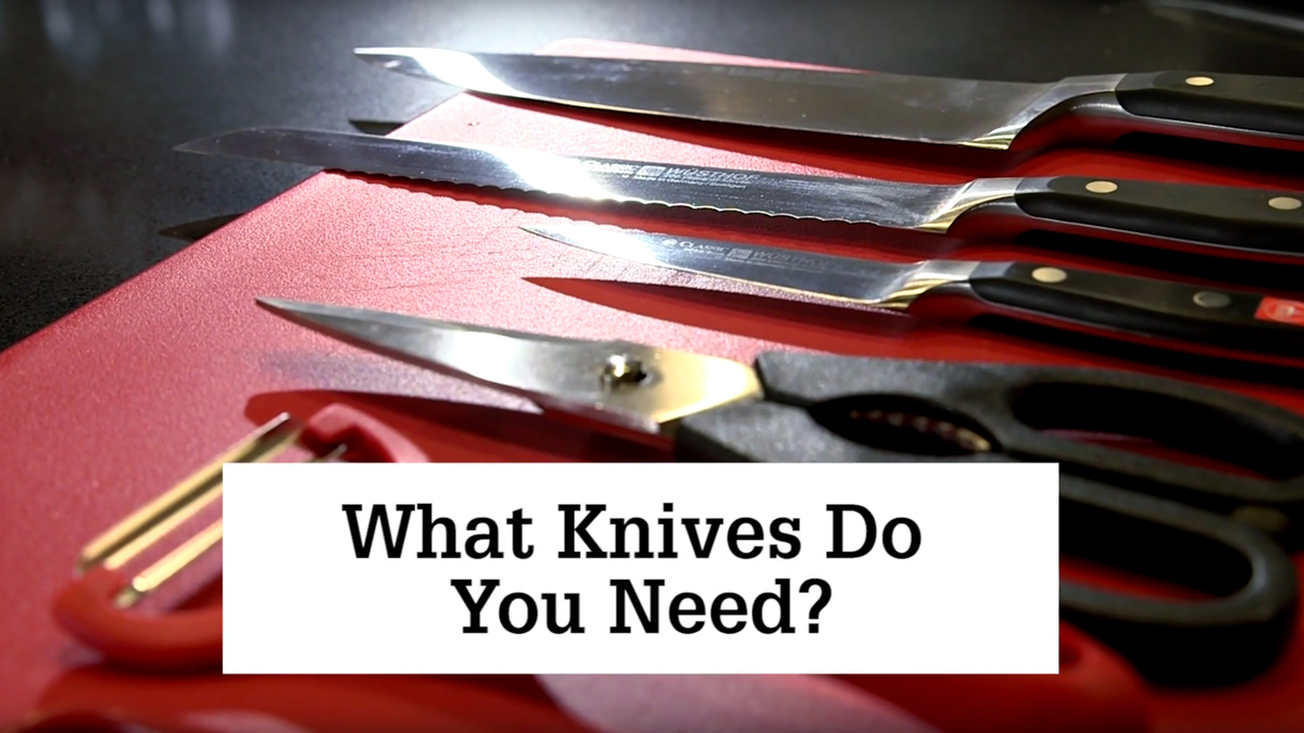 """A set of kitchen knifes are laid out on a red cutting board with text overlay that reads: """"What knives do you need?"""""""