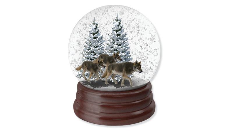 A snowglobe with wolfs, trees and falling snow inside