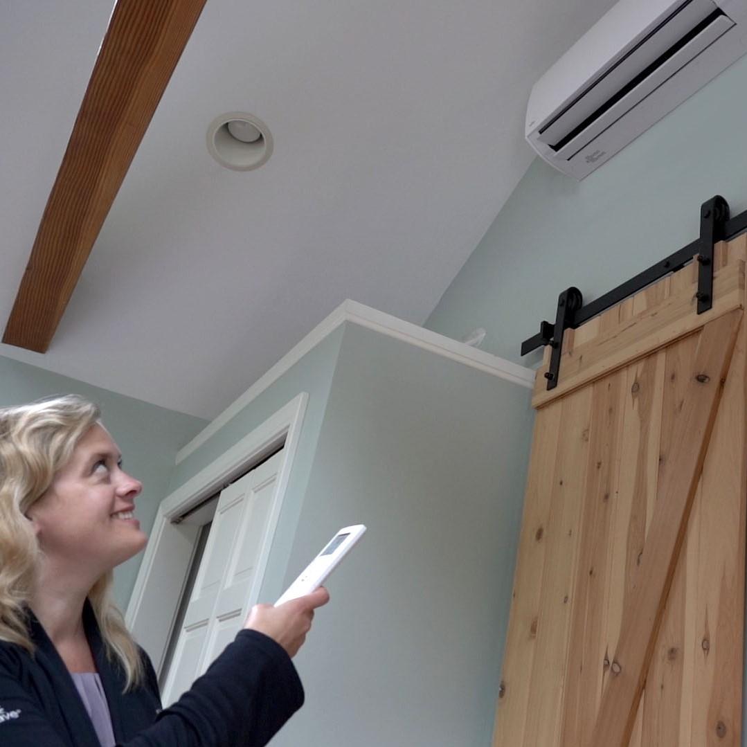 Person adjusting heat pump settings