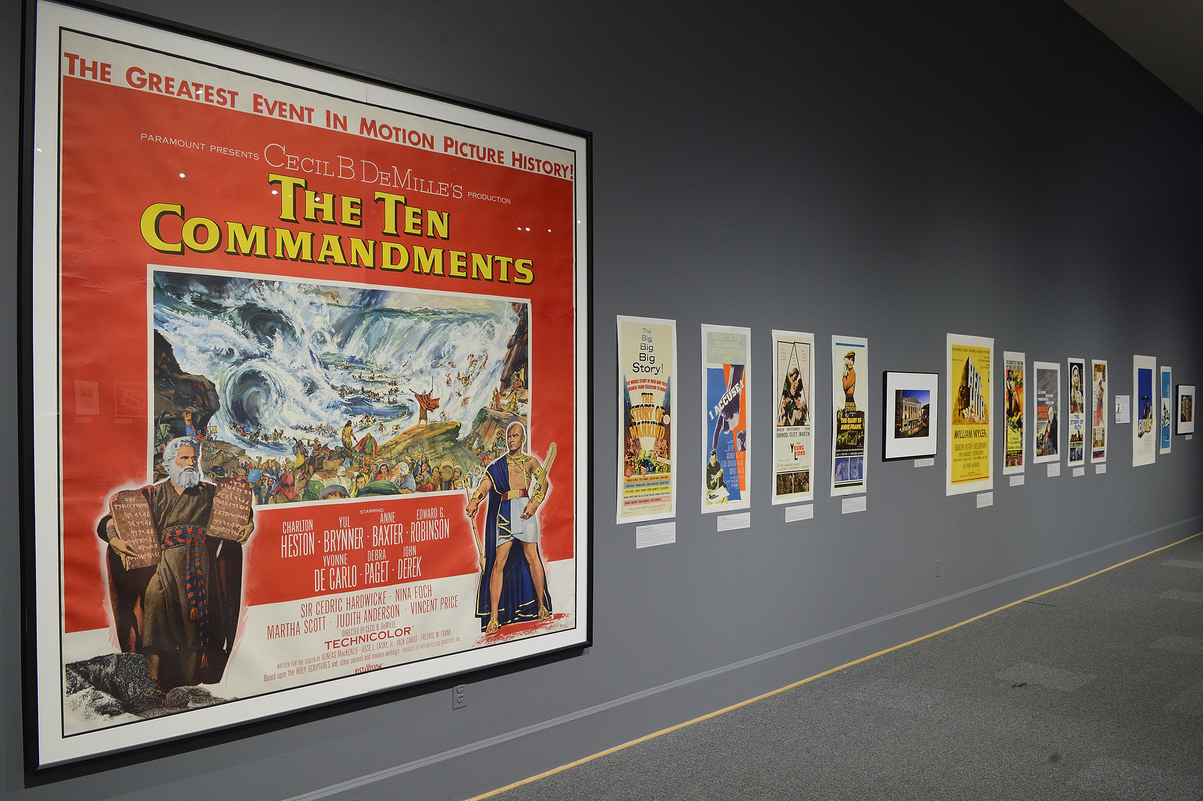 View down wall of various film posters, starting with large 10 Commandments