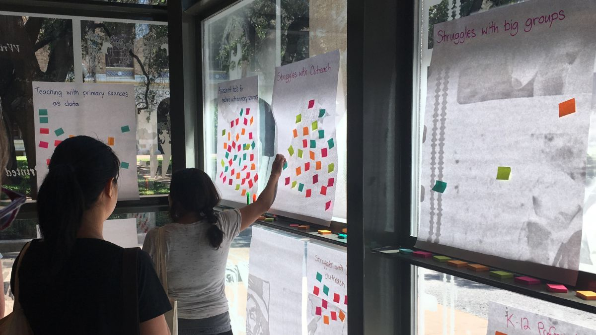 People placing post-it notes on large pieces of paper to vote on unconference sessions