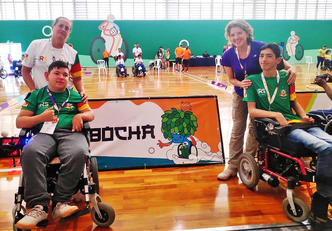 Em um ginásio, foto de dois estudantes em cadeiras de rodas com os professores