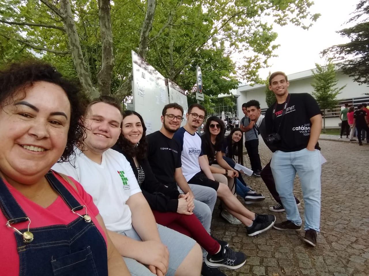 Grupo de alunos no pátio de uma escola sorrindo para a câmera