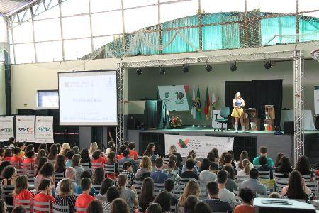 Foto de apresentação teatro em um ginásio lotado de estudantes