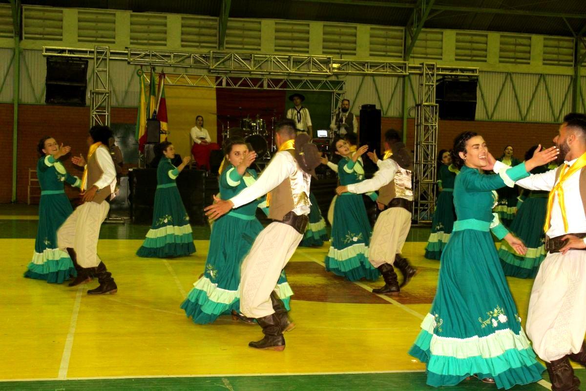 Foto de casais pilchados dançando em um ginásio