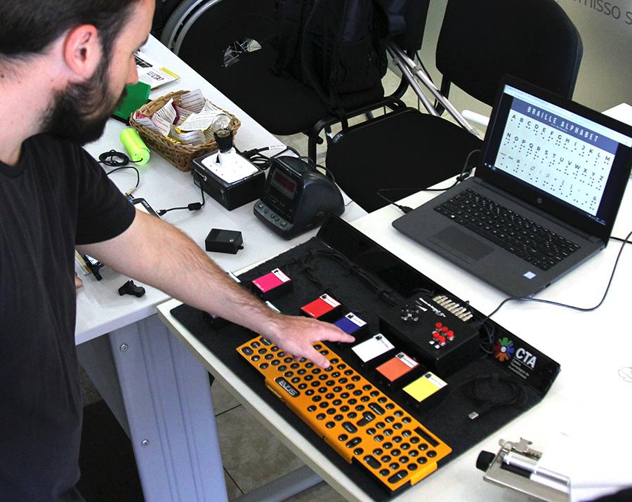 Servidor do IFRS mostra aparelhos de tecnologia assistiva em uma mesa